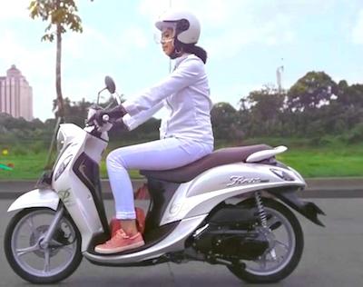 Woman riding a motorbike scooter at snake internship in Krabi, Thailand.